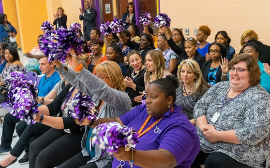 Teachers at Barack Obama Learning Academy cheering during principal's Curriculum Night introductions.