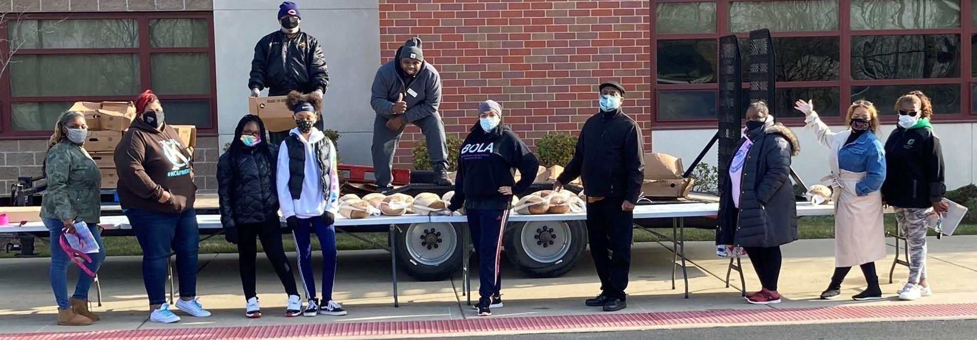 School Board President Dean Barnett, Superintendent Dr. Spells and staff serving the community with free turkeys.