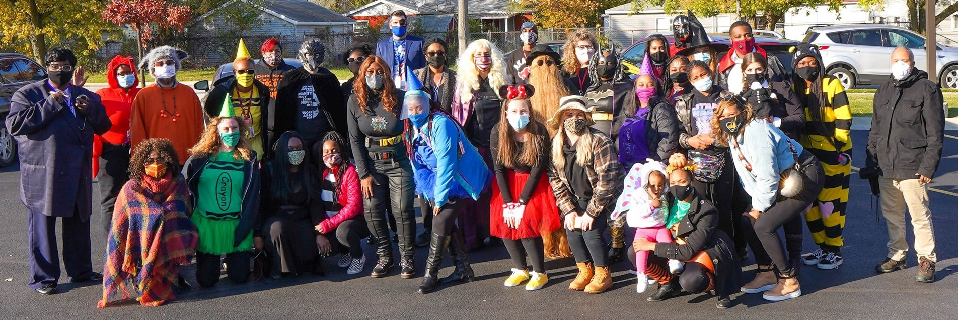 Jesse White Staff pose after giving treats to their students during Trunk or Treat festivities